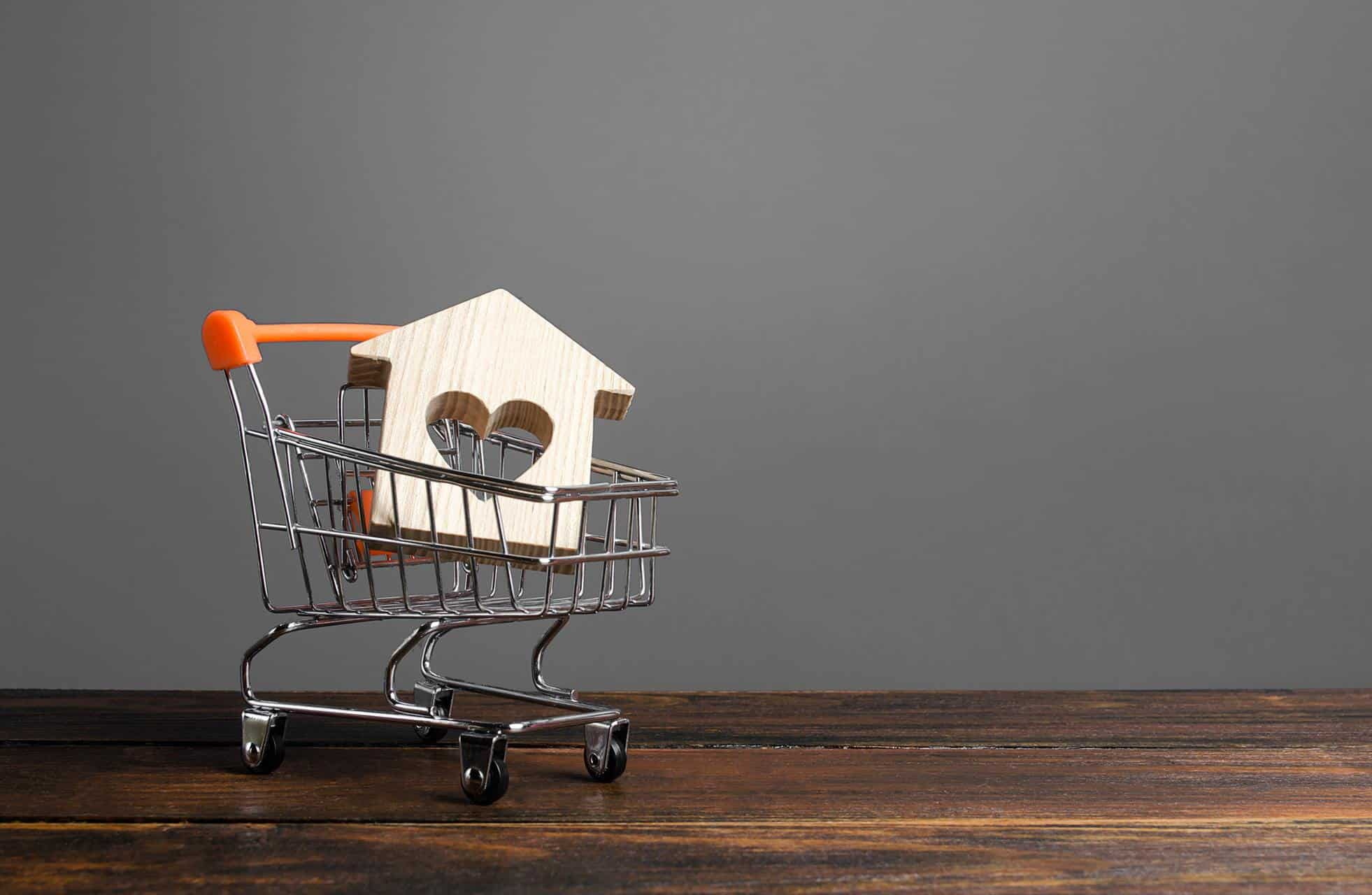 tiny wooden house shape with a heart in a mini shopping cart to reflect blog topic, titled mortgage renewal: shopping for a better mortgage rate?